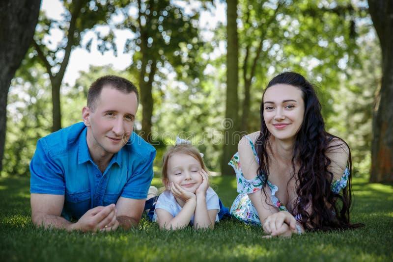 愉快的快乐的年轻家庭父亲、母亲和小女儿获得乐趣户外,一起使用在夏天公园 妈妈 图库摄影