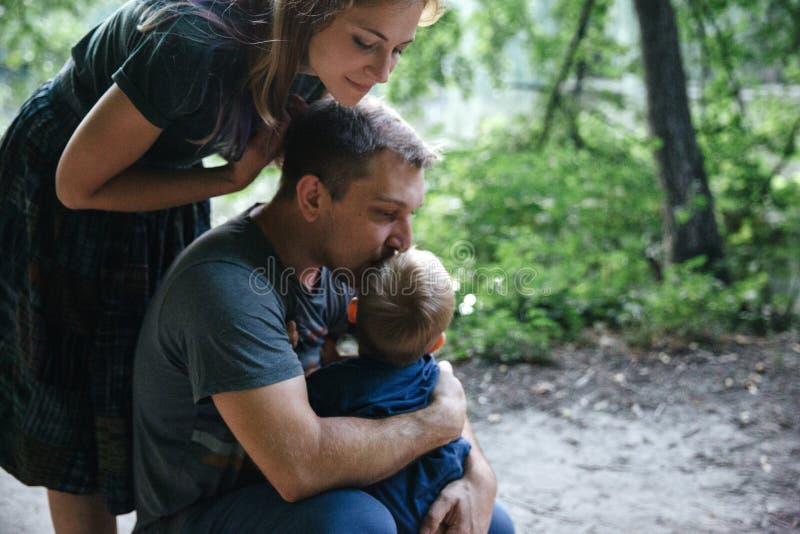 愉快的快乐的年轻家庭父亲、的母亲和亲吻小的儿子拥抱和户外,一起使用在夏天公园 免版税库存照片