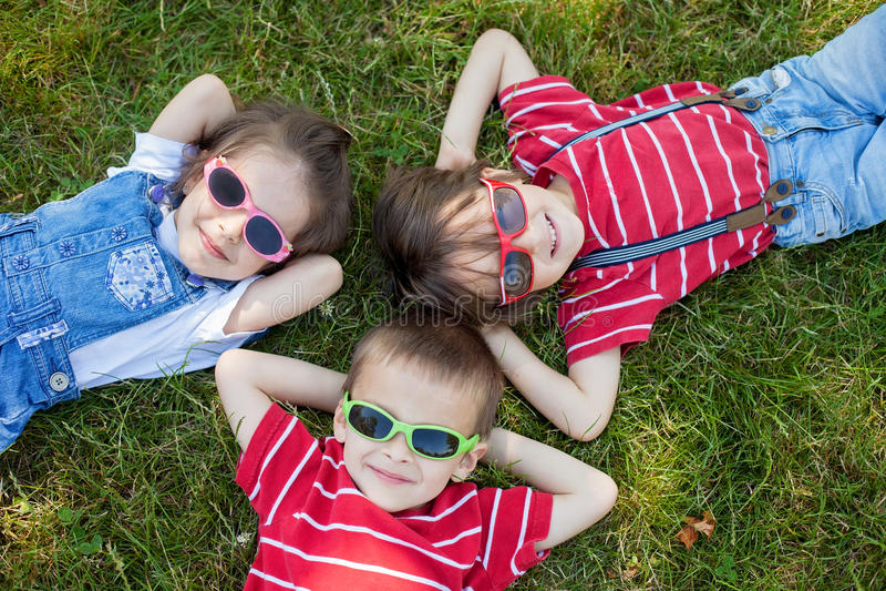 愉快的快乐的微笑的孩子,放置在草,唱歌的佩带 库存图片