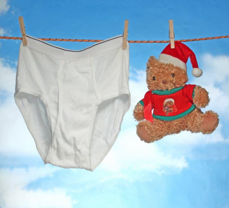 愉快的快活的X mas垂悬的男性裤子和圣诞老人帽子 免版税库存照片