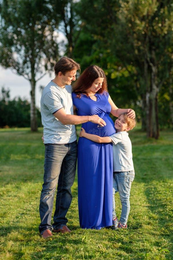 愉快的怀孕的三口之家期望的新的婴孩 图库摄影