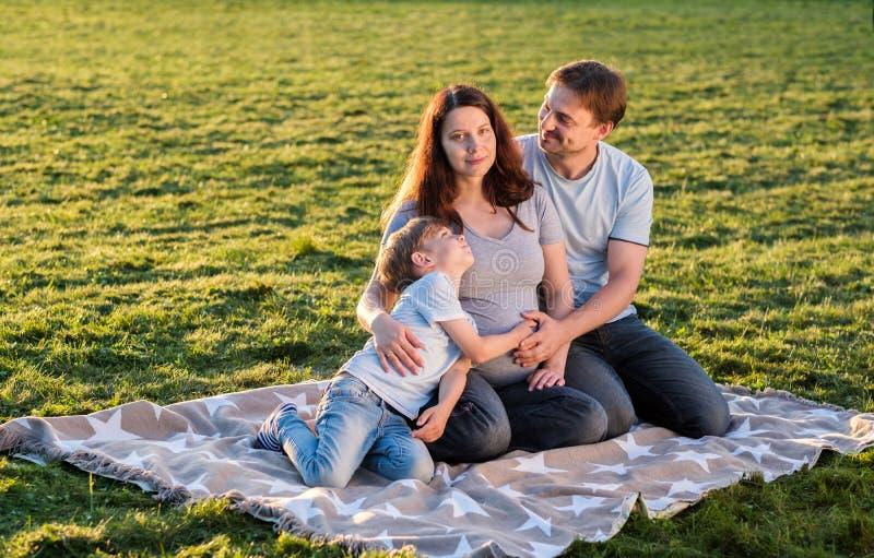 愉快的怀孕的三口之家期望的新的婴孩 库存照片