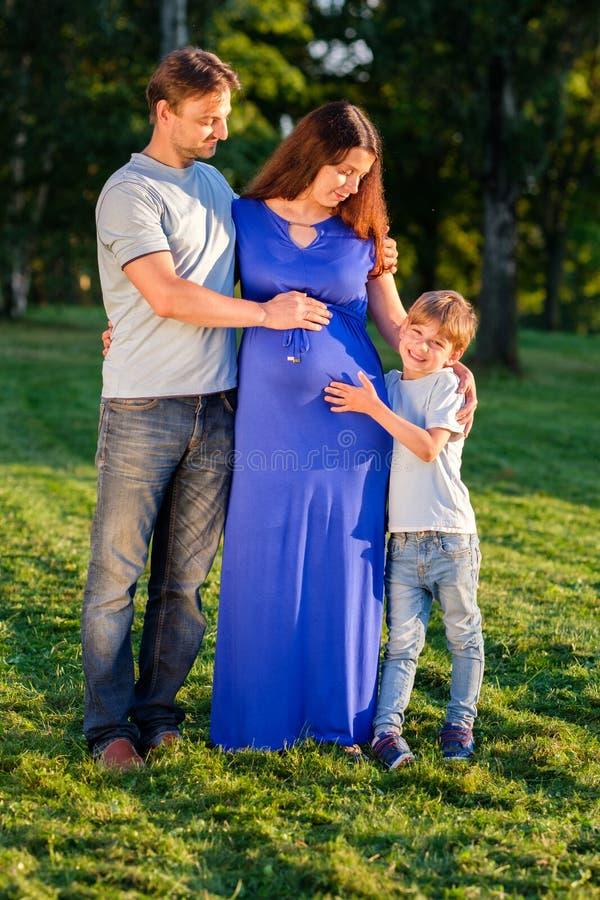 愉快的怀孕的三口之家期望的新的婴孩 免版税图库摄影