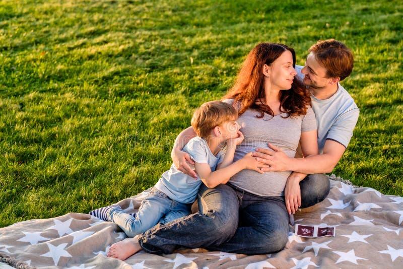 愉快的怀孕的三口之家期望的新的婴孩 库存图片