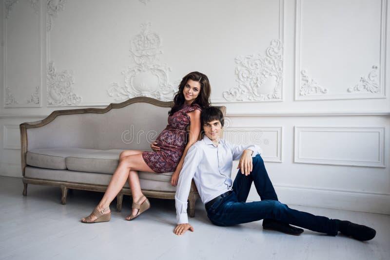 愉快的怀孕的夫妇在家,年轻爱恋的家庭人怀孕、期待婴孩的画象和妇女在家坐 库存照片
