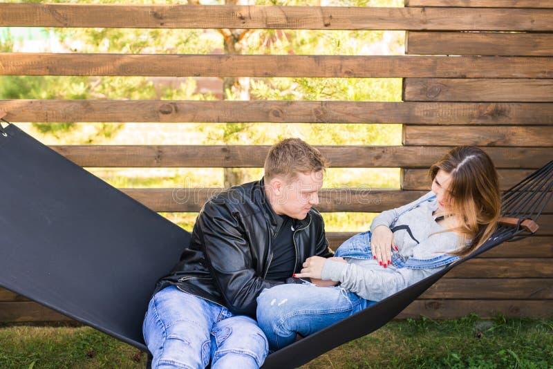 愉快的怀孕的夫妇坐在吊床的-家庭、父母身分和幸福概念 免版税库存照片