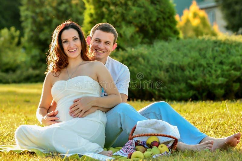 愉快的怀孕的夫妇坐草在公园 库存照片