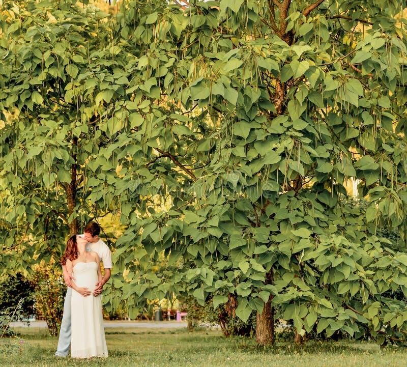 愉快的怀孕的夫妇坐banch在公园 免版税库存照片