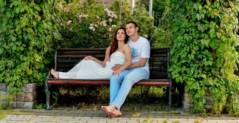 愉快的怀孕的夫妇坐banch在公园 免版税库存图片