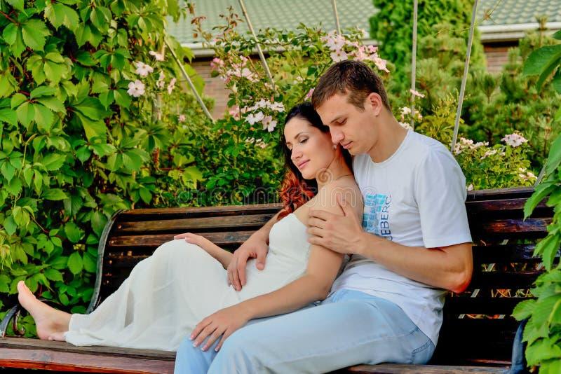 愉快的怀孕的夫妇坐banch在公园 库存照片