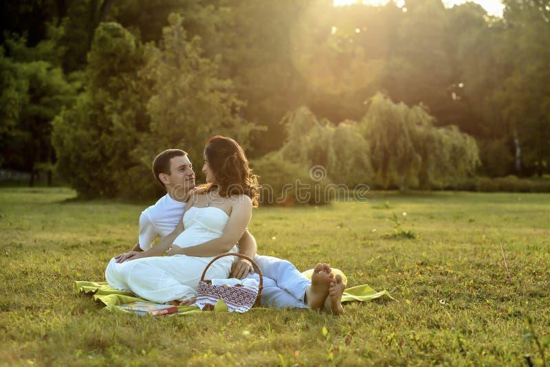 愉快的怀孕的夫妇坐banch在公园 库存图片