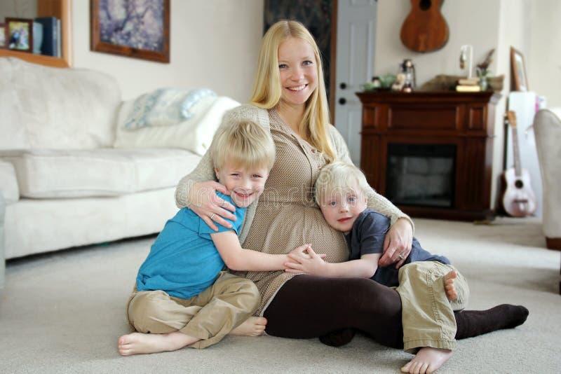愉快的怀孕的母亲和她的两个幼儿在家 免版税库存照片