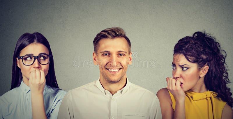 愉快的急切地看他的男人和两名不安全的妇女 库存照片
