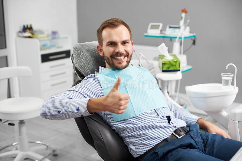 愉快的患者画象牙齿椅子的,展示打手势类 免版税库存图片