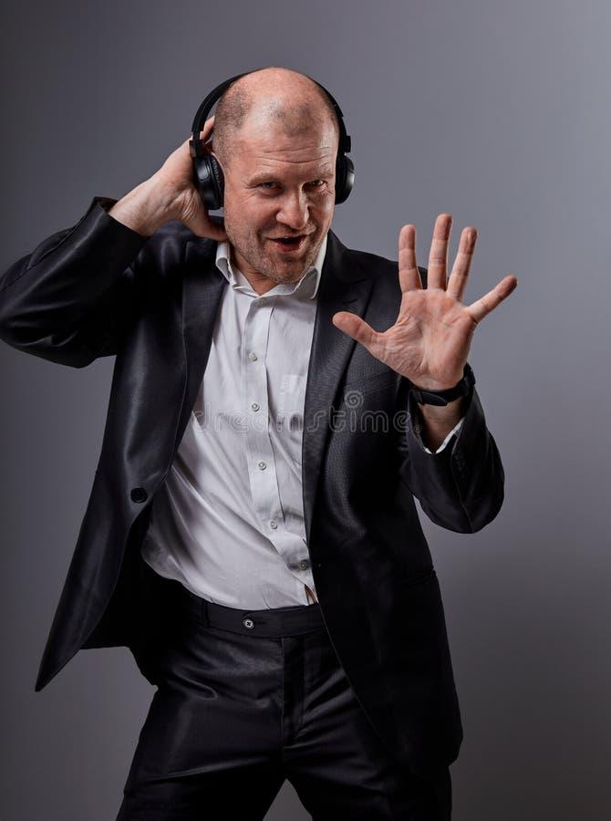 愉快的情感听在无线耳机的音乐在深灰背景和显示五的跳舞和唱歌的秃头人 免版税库存照片