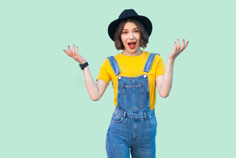 愉快的惊奇的俏丽的少女画象蓝色牛仔布总体、黄色衬衣,黑帽会议身分和看的照相机与 库存图片