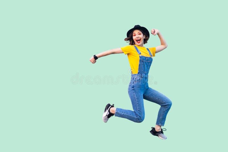 愉快的惊奇的俏丽的年轻行家女孩画象蓝色牛仔布总体、黄色跳跃和看的衬衣和黑帽会议的 免版税库存照片