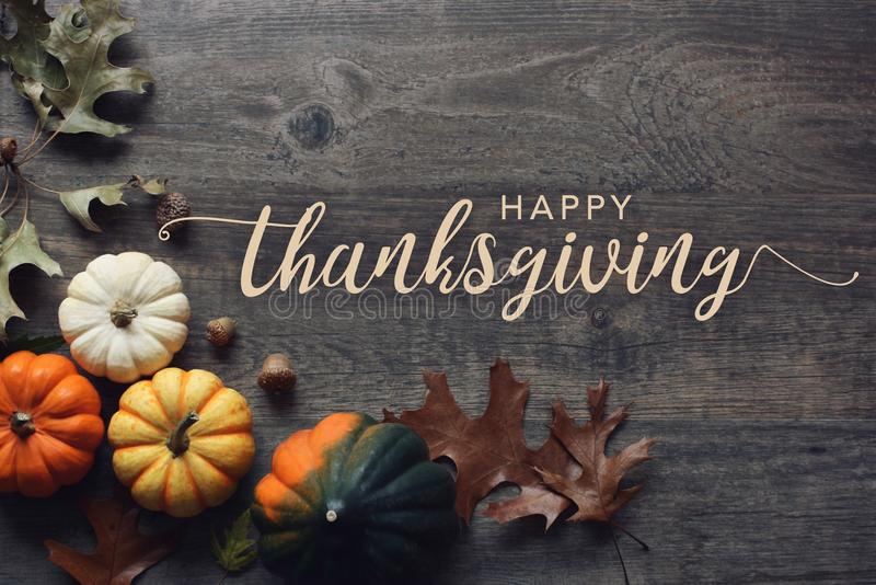 愉快的感恩问候文本用南瓜、南瓜和叶子在黑暗的木背景 免版税图库摄影