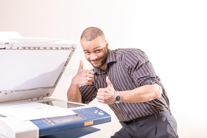 愉快的成功的人在影印机附近的办公室 库存图片