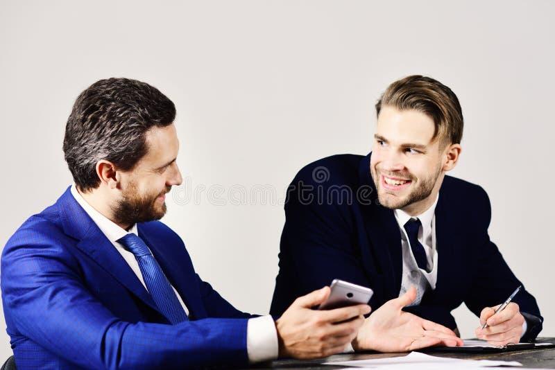 愉快的成功的企业和计划概念 有愉快的面孔的经理谈论并且浏览互联网 库存图片
