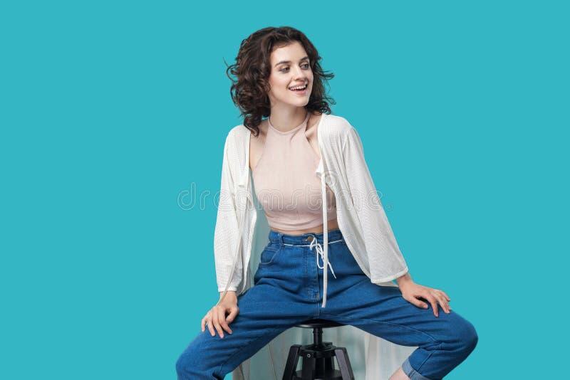 愉快的成功的满意的美丽的年轻深色的妇女画象便装样式的坐椅子,暴牙微笑和看 免版税库存照片