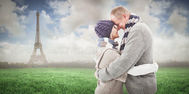 愉快的成熟夫妇的综合图象在冬天给拥抱穿衣 免版税库存图片