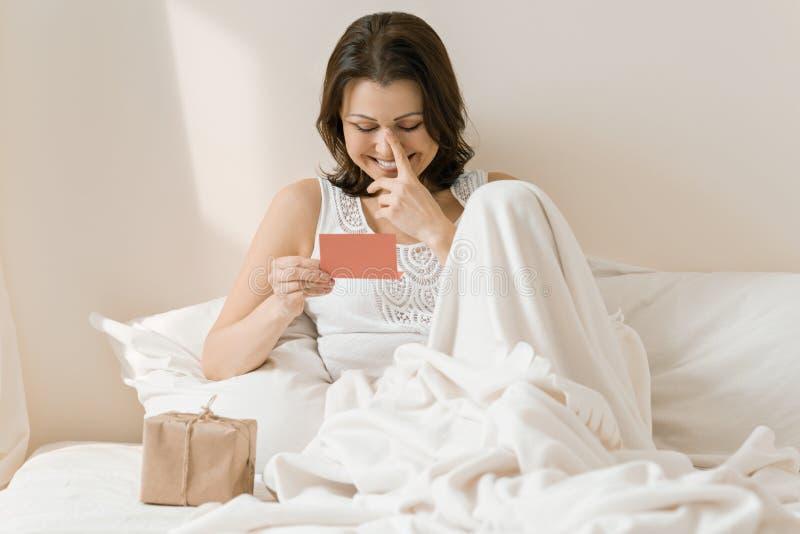 愉快的成熟妇女在家在与惊奇礼物读书贺卡的床上 幸福,喜悦,惊奇的情感 图库摄影