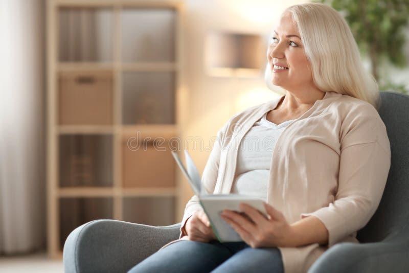 愉快的成熟妇女阅读书,当坐在扶手椅子时 免版税图库摄影