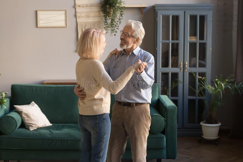 愉快的成熟爱恋的夫妇、在家跳舞妻子和的丈夫 库存照片