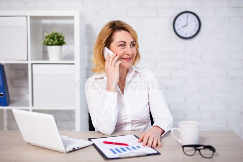 愉快的成熟的商业妇女坐在办公室和谈话由电话 库存照片
