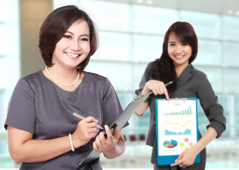 愉快的成熟的商业妇女,当她的助理显示图 免版税库存照片