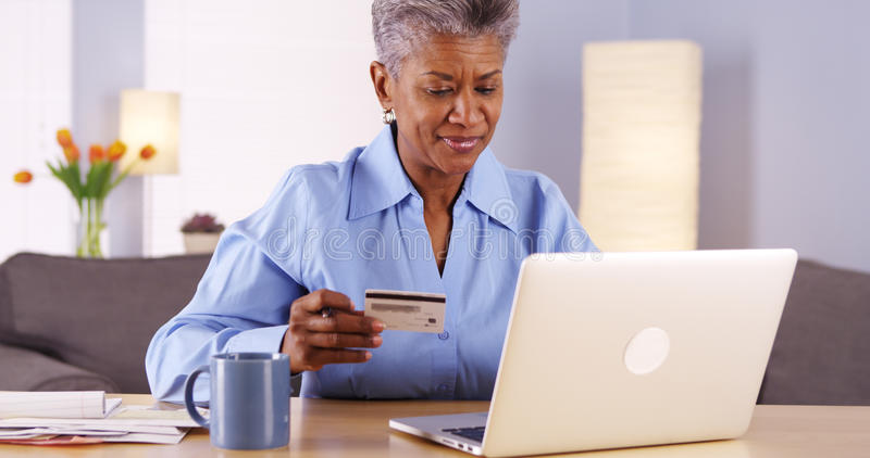 愉快的成熟非洲妇女买的事在网上 免版税图库摄影