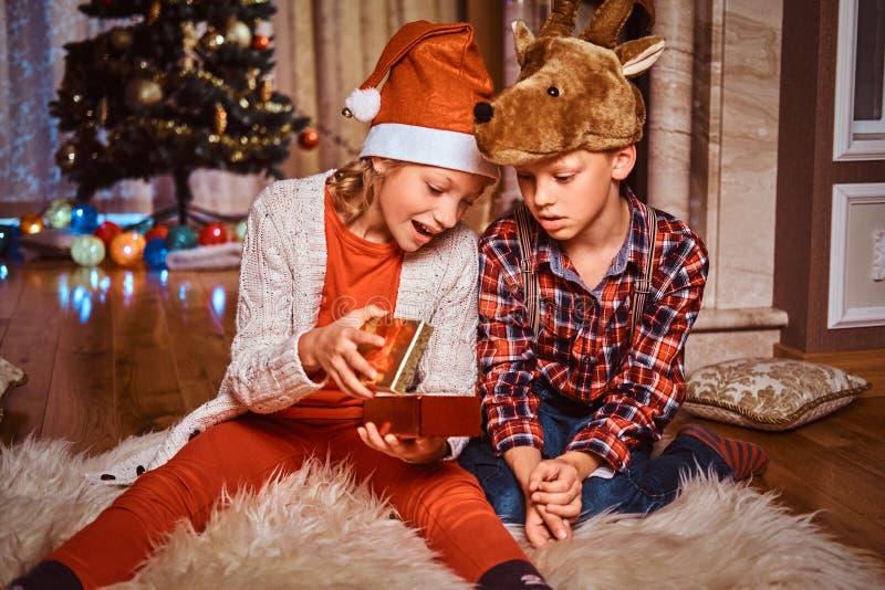 愉快的戴圣诞老人和鹿帽子的兄弟和姐妹坐毛皮地毯和在圣诞树附近打开礼物在 图库摄影