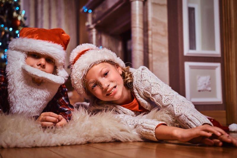 愉快的戴圣诞老人帽子的兄弟和姐妹在家说谎在毛皮地毯在圣诞树附近 免版税库存图片