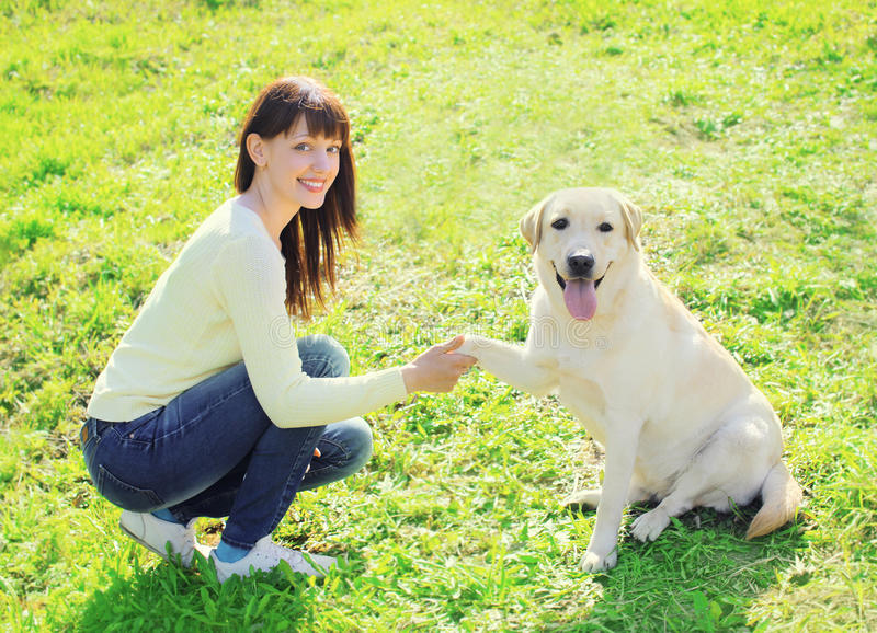 愉快的所有者妇女和拉布拉多猎犬狗火车 免版税库存图片