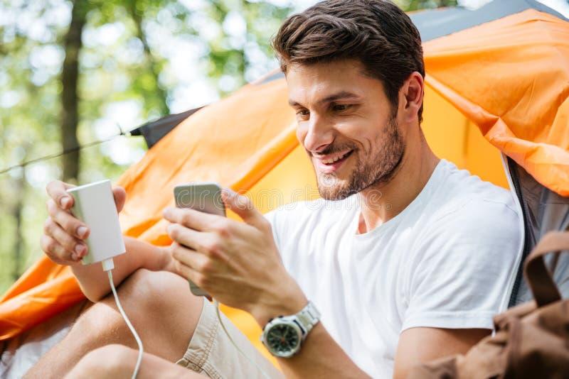 愉快的手机人旅游充电的电池在森林里 免版税图库摄影