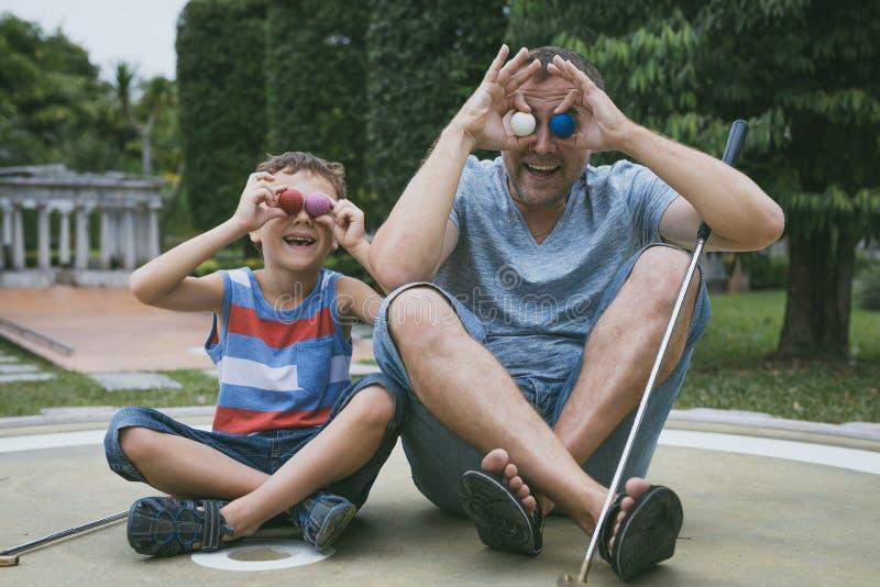 愉快的打微型高尔夫球的父亲和小儿子 免版税库存照片