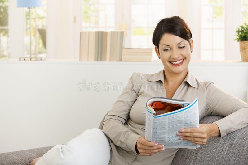 愉快的报纸读取沙发妇女 免版税图库摄影