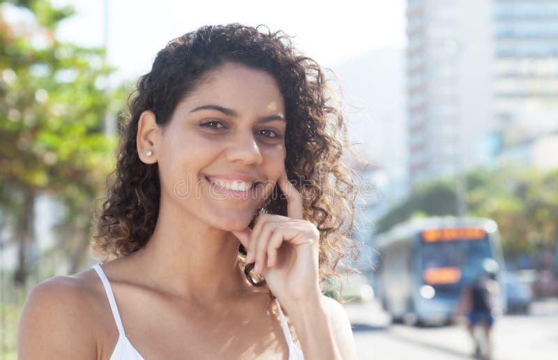 愉快的拉丁妇女外面在看照相机的城市 免版税库存图片