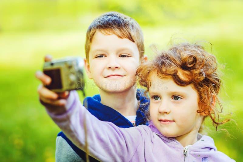 愉快的拍自已照片的小男孩和女孩在秋天公园 免版税库存图片
