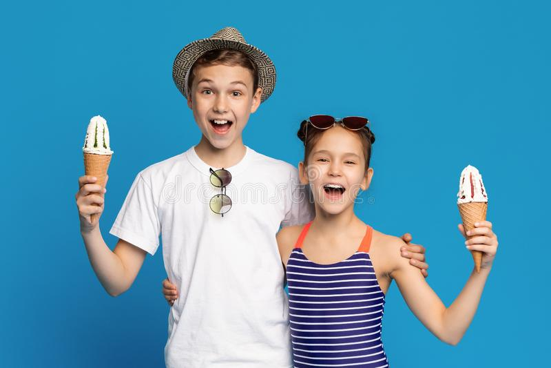 愉快的拥抱与冰淇淋锥体的小男孩和女孩 库存照片