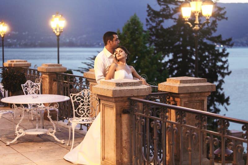 愉快的拥抱在平衡的阳台的夫妇丈夫和妻子近 免版税库存照片