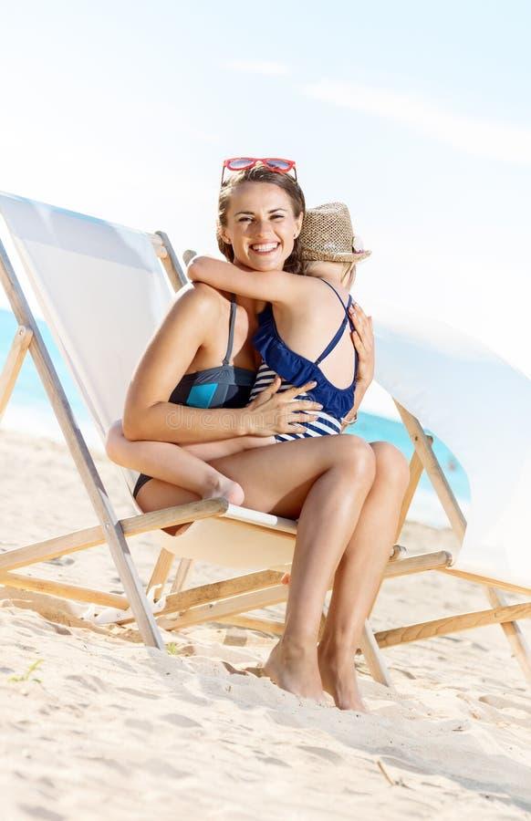 愉快的拥抱母亲和的孩子,当坐海滩睡椅时 库存图片