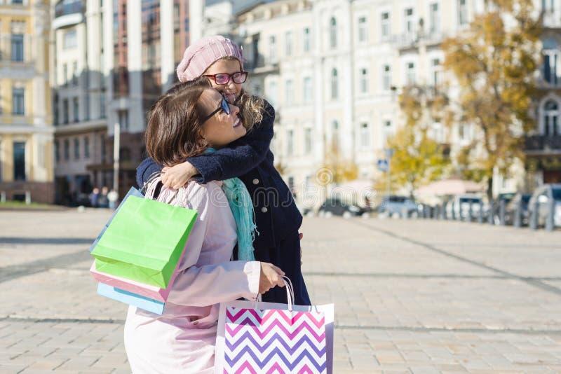 愉快的拥抱,与购物袋,都市样式背景的母亲和女儿 库存照片