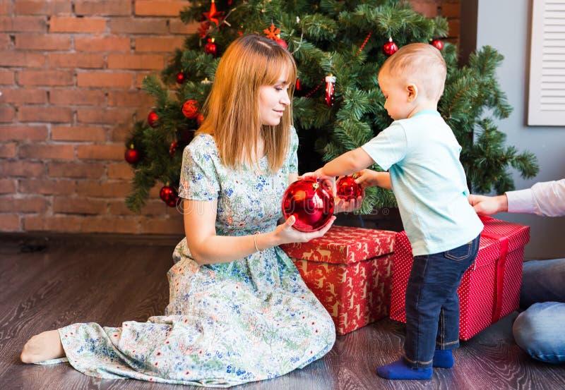 愉快的拿着中看不中用的物品的母亲和可爱的婴孩反对与圣诞树的国内欢乐背景 免版税库存图片