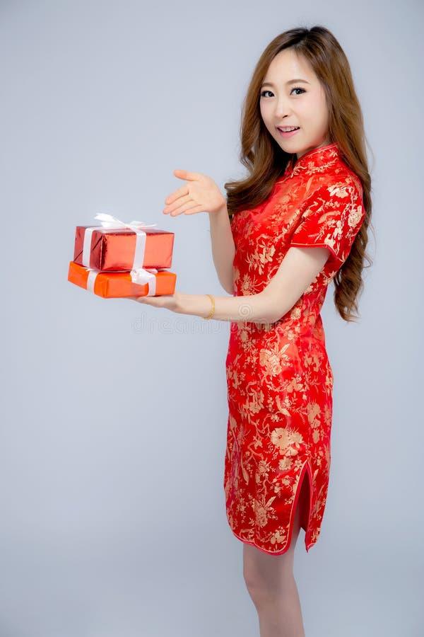 愉快的拿着在白色背景的农历新年美丽的画象年轻亚裔妇女红色礼物盒 库存照片