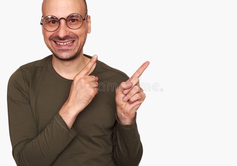 愉快的指向手指的人佩带的眼镜 免版税库存照片