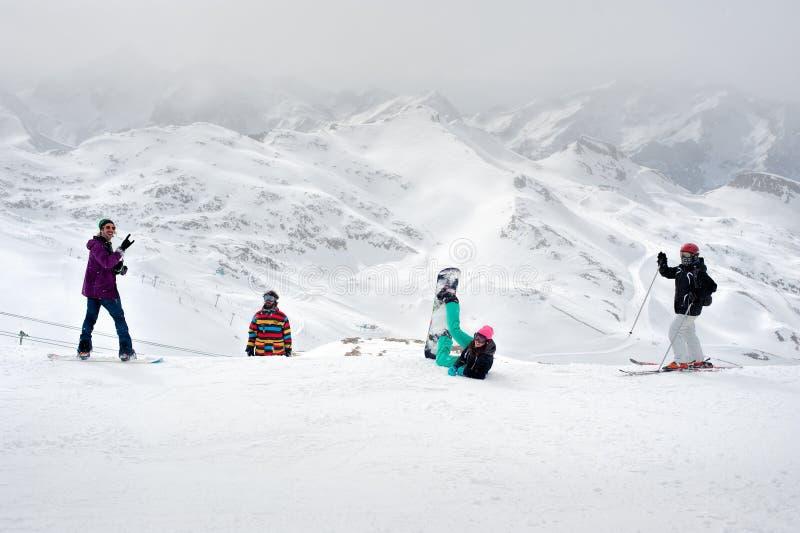 愉快的挡雪板和滑雪者享用在山顶部 免版税图库摄影