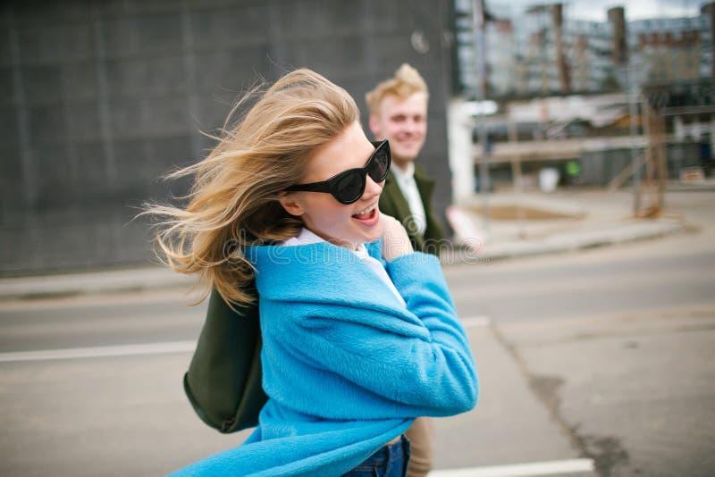 年轻愉快的握在爱的夫妇走的城市街道手 免版税库存图片