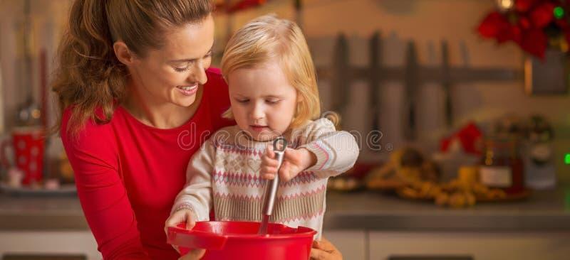 愉快的搅拌面团的母亲和婴孩在圣诞节厨房里 免版税图库摄影